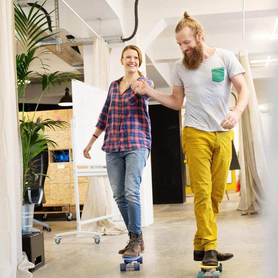 Kaksi henkilöä skeittaa iloisena toimistossa.
