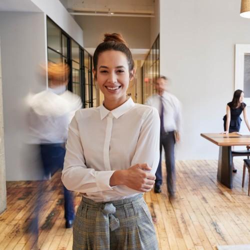 Kuvassa hymyilevä nainen lähikuvassa toimistolla