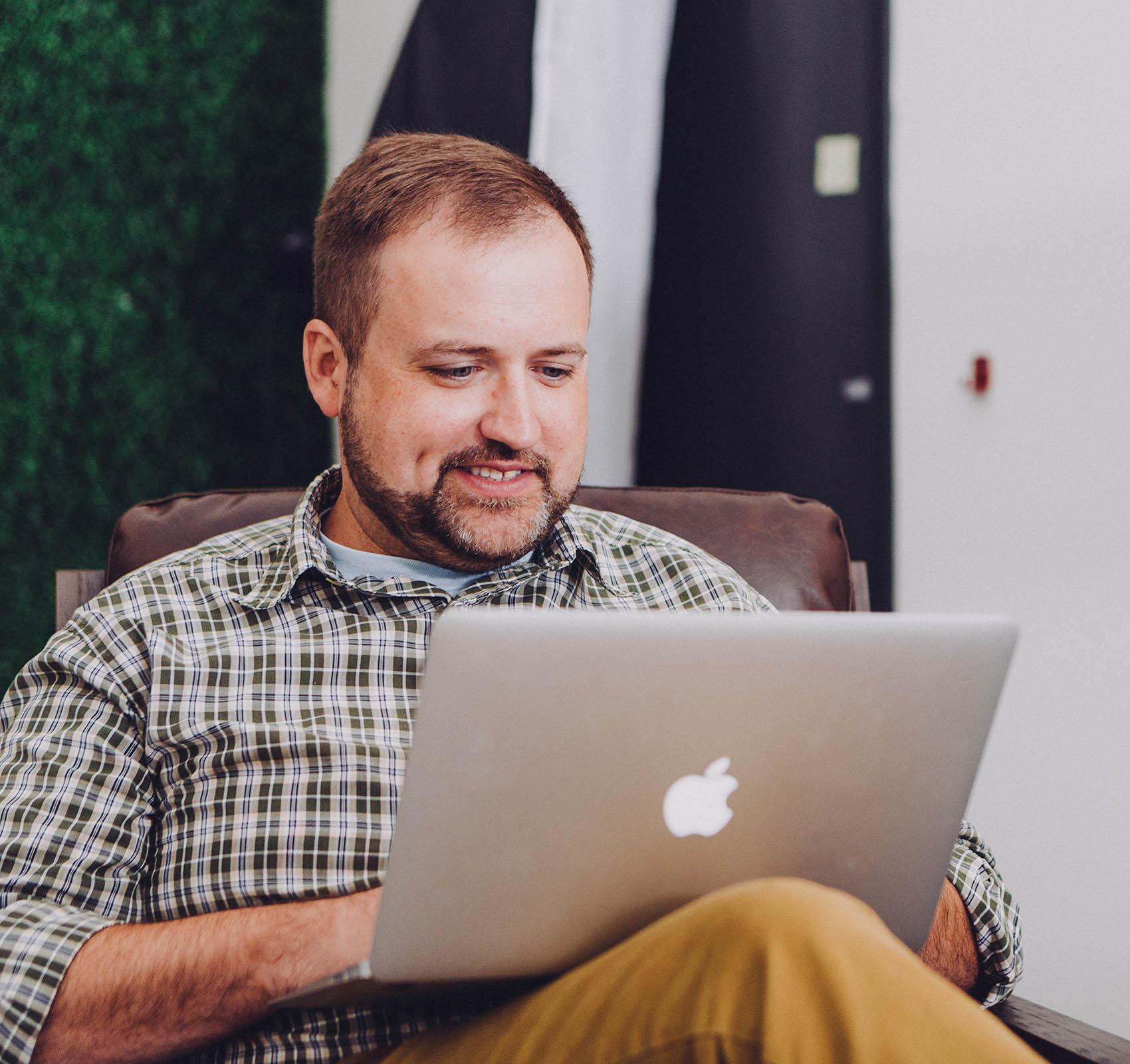Kuvassa parrakas mies istuu penkillä ja naputtelee tietokoneellansa