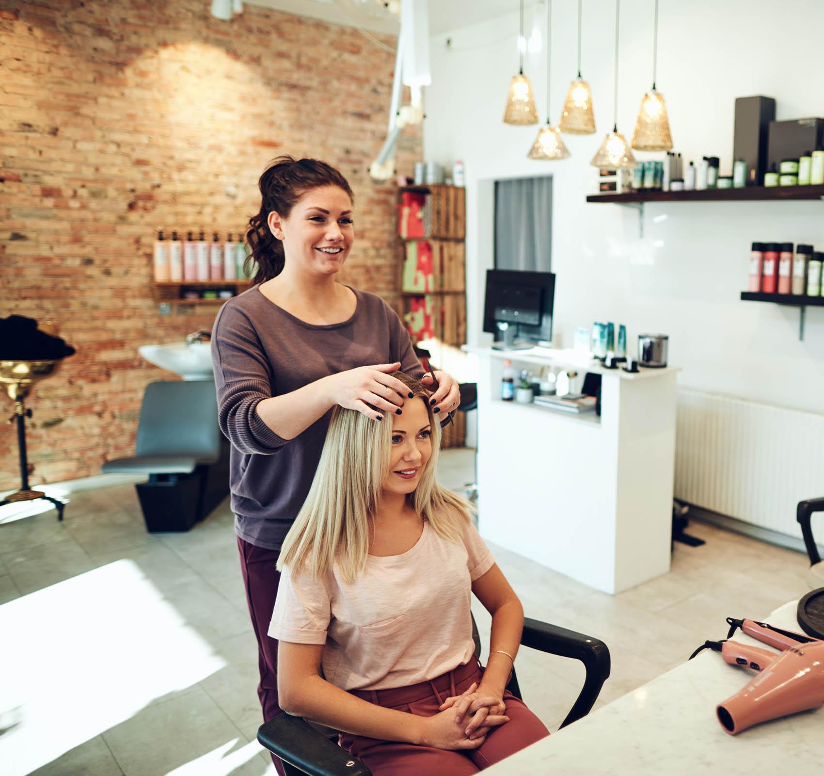 Kuvassa kampaaja viimeistelemässä asiakkaansa hiuksia