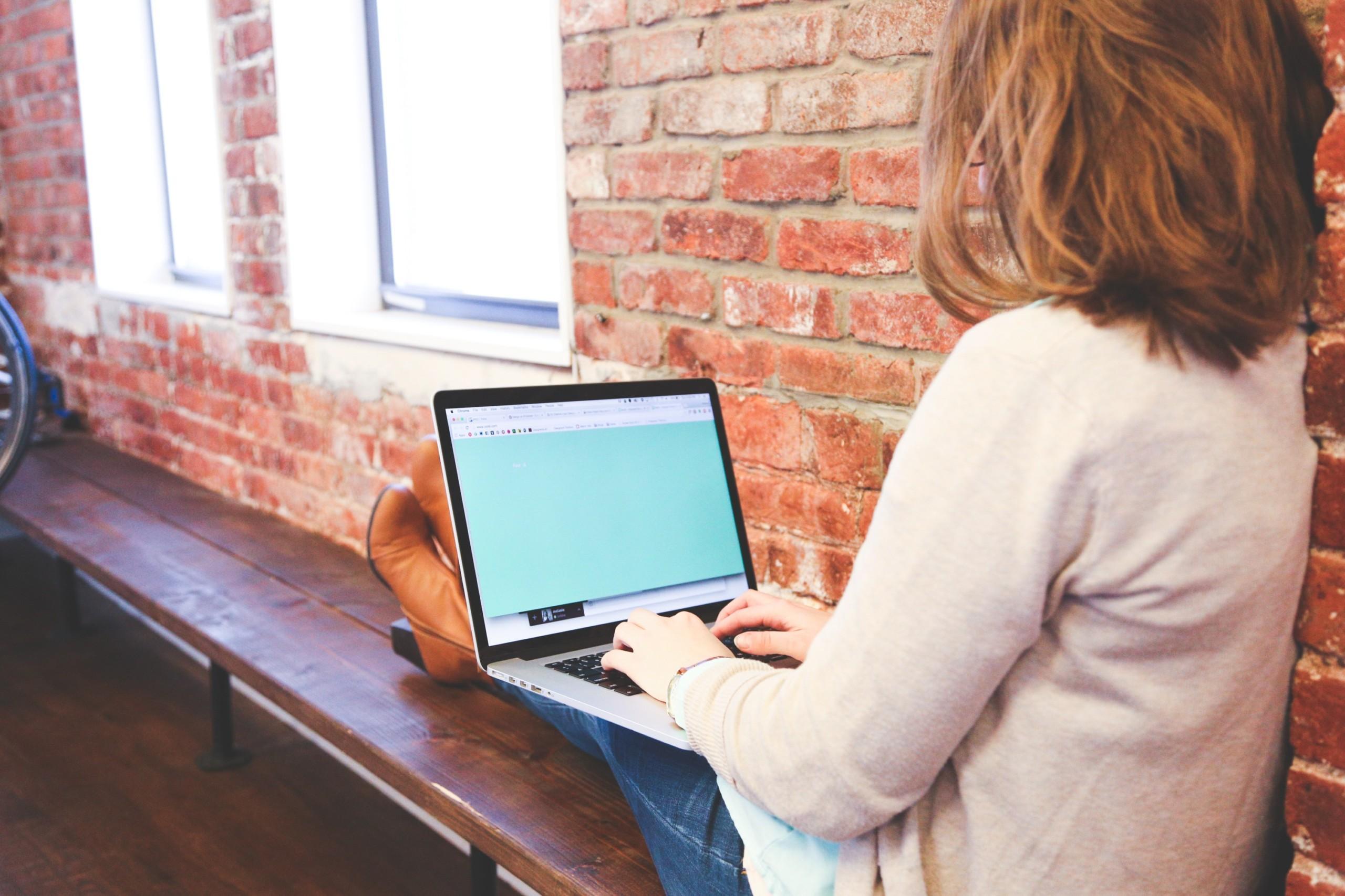 Nainen istuu tietokoneen ääressä opiskellen.