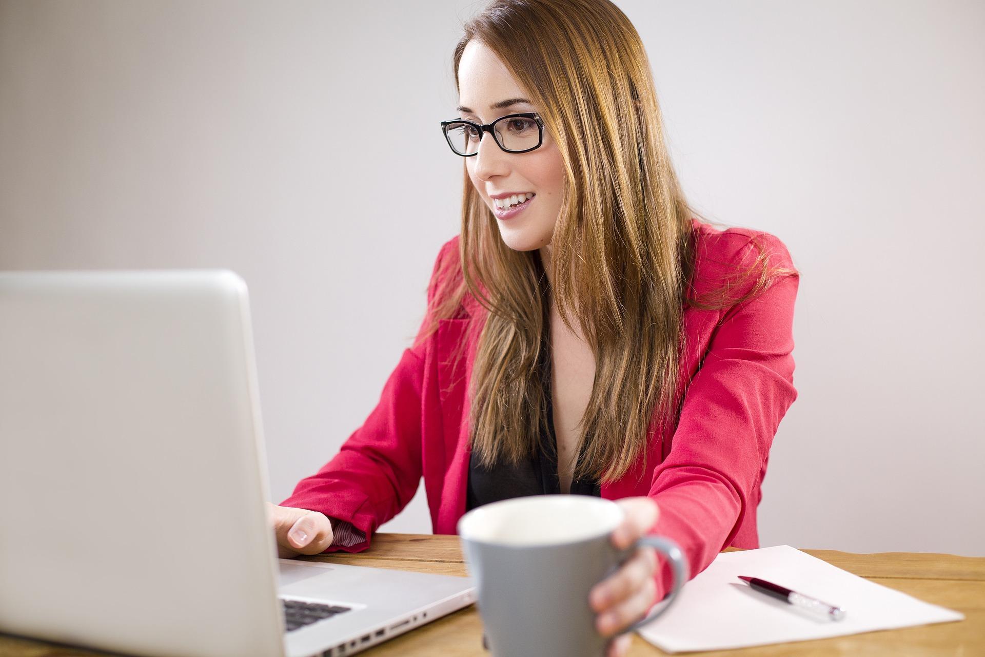 Puna-asuinen, pitkähiuksinen nuori nainen työskentelee tietokoneella.