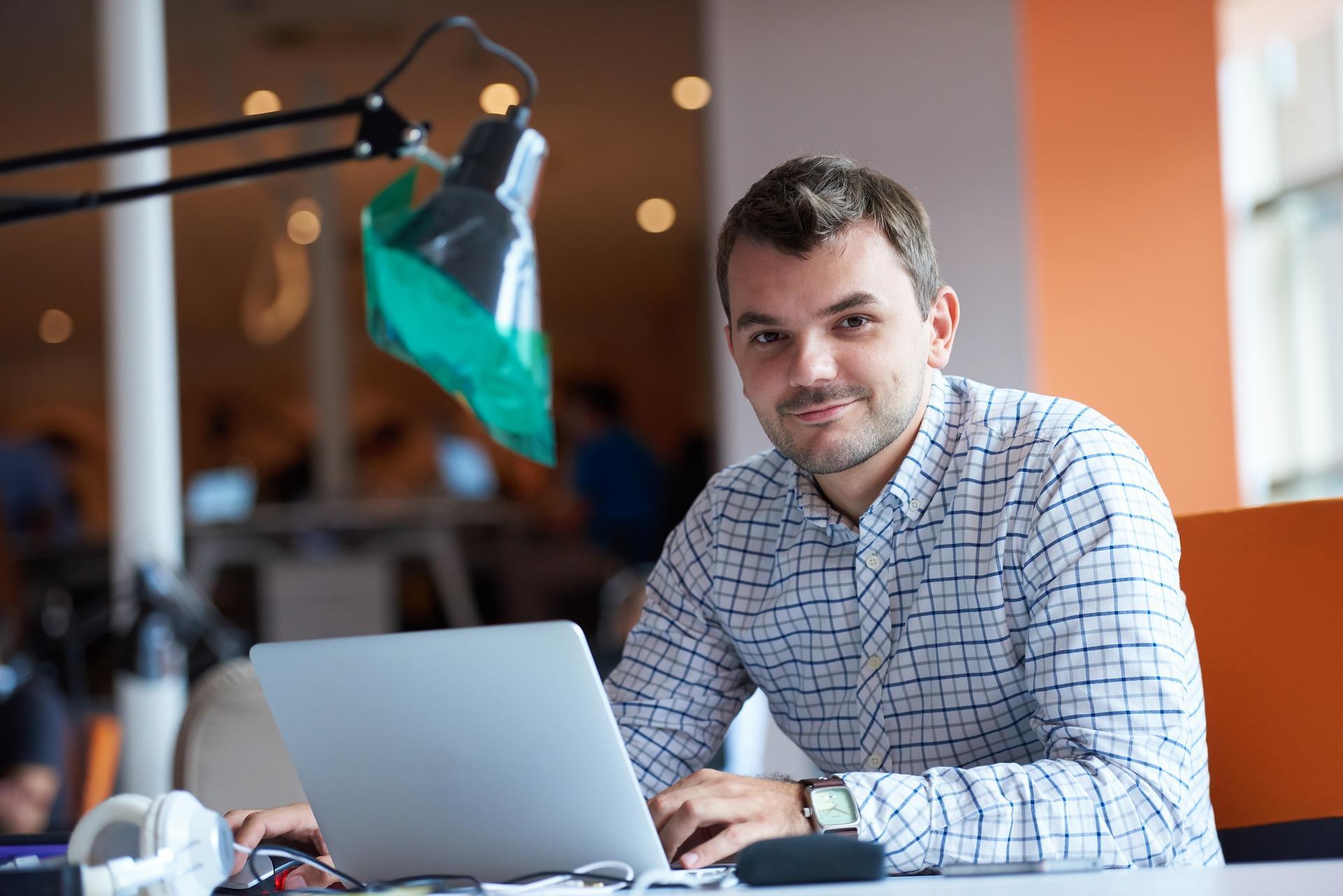 Ruutupaitainen mies tietokoneen ääressä.